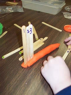 """Write the numbers 0-10 on a set of lolly sticks. To add extra support, draw dots on the lolly sticks to match the number written on them. Children line up the numbers and stick them in the playdough ("""",)"""
