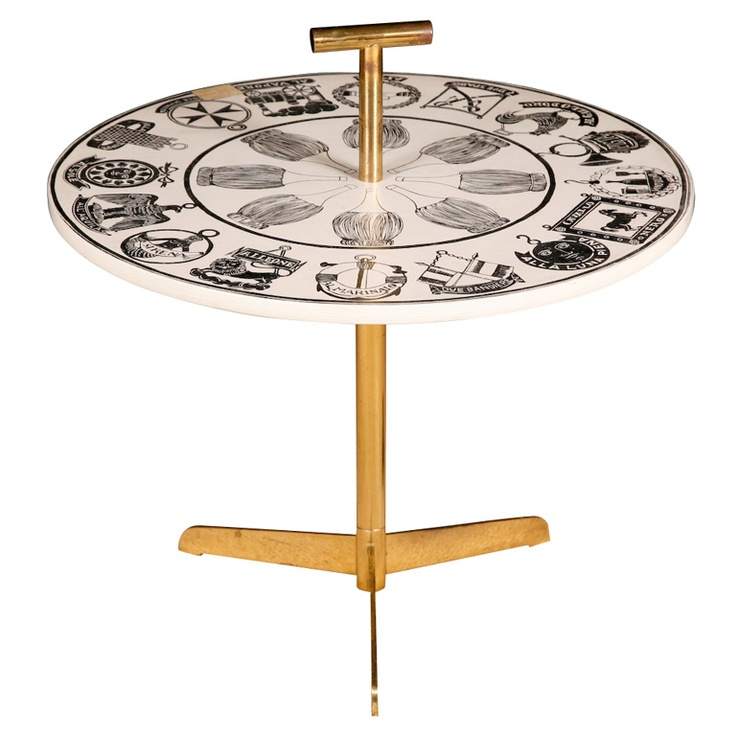 "An Occasional Table with brass carrying handle by Piero Fornasetti. ""Insegne Osterie"" White ground with black labels. Lithographically printed Brass handle and brass tripod base. Label to base, Archive label. 50cms high x 60cms diam Italy, circa 1960. prev           next TITLE:	 An Occasional Table with brass carrying handle by Fornasetti PRICE:	$7,000 Purchase  CREATOR:	 Piero Fornasetti (Designer) COUNTRY:	 Italy CREATION DATE:	 Circa 1960 MATERIALS:	 Lithographically printed wood. Brass…"