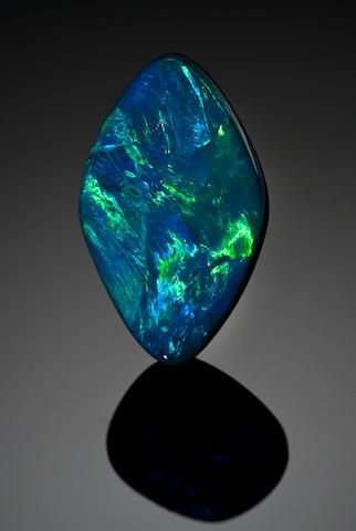 """""""Unique and Classic Black Opal Lightning Ridge, Australia This unique and unusual cabochon of true black opal has been fashioned by the gem cutter as in a lozenge-shaped outline--a rather unusual and elegant shape.  The body color is a true black, with vibrant and vivid play-of-color in blues and greens, characteristic for the region, with classic potch on the reverse, weighing approximately 26.88 carats""""  © Bonhams (quote) via bonhams.com"""