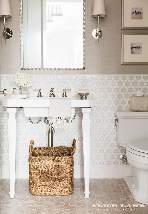 Welcoming white and gray transitonal powder room is lit by Thomas O'Brien Bryant Sconces mounted on either side of a silver mirror fixed to a wall half covered in gray grasscloth wallpaper.