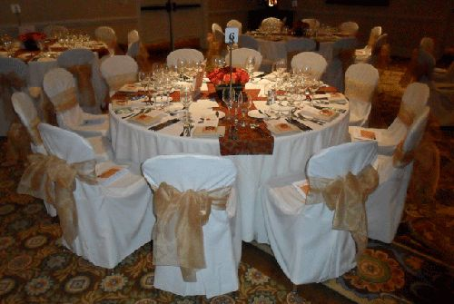 Gold Bows at white chair covers for rent - Special Event Linens.