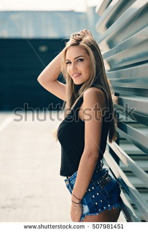Sexy young girl wearing high waisted shorts and black top posing near a depot storage storehouse metal wall outside in the sunlight.