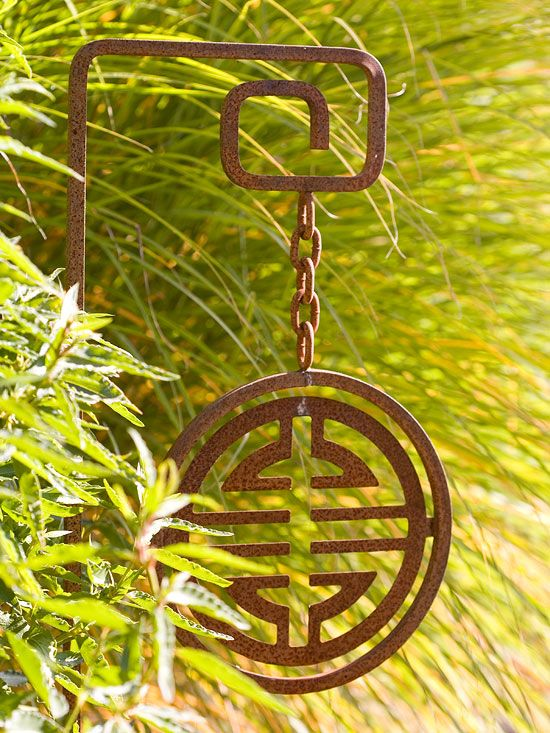 Add a few accents to your landscape that reflect your personality. This iron medallion waves in the wind and gives a large patch of ornamental grass an intriguing artistic element. Test Garden Tip: Ornaments such as this can also act as hose guides -- place them at the edge of your border to keep your watering hose from crushing plants as you pull it around corners.