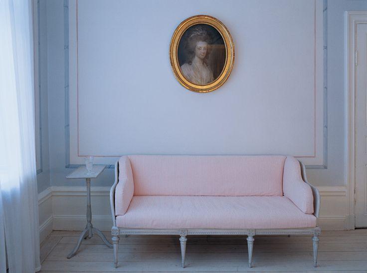 Den Gustavianska trågsoffan är gjord efter ett original från 1782. Ovanför hänger ett porträtt signerat 1786 av Elias Martin.
