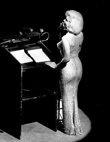 "Marilyn Monroe at the microphone singing ""Happy Birthday, Mr. President,"" at President John F. Kennedy's birthday bash, May 19, 1962."