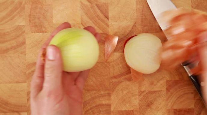 Een ui snijden en snipperen. We snijden op een veilige manier de ui en vervolgens maken we mooie, kleine ui snippers. In het filmpje van Allerhande worden de stappen duidelijke uitgelegd. In het instructiefilmpje zie je dat we eerst de ui door midden snijden en vervolgens pellen. Vouw je vingerkootjes naar binnen bij het ui snijden en houd je duim en pink achter de andere vingers.