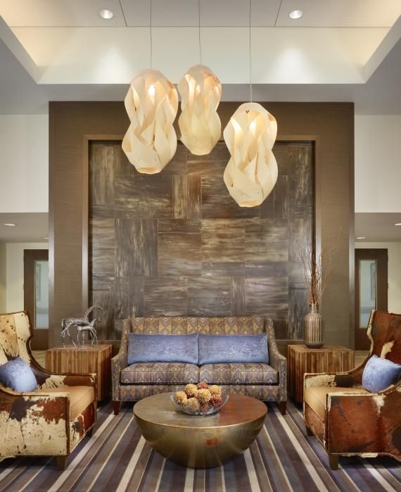 Hanging pendants, a wood feature wall, and warm, neutral colors create a homey feel at Air Force Village, a senior living community in San Antonio. Photo credit: Casey Dunn