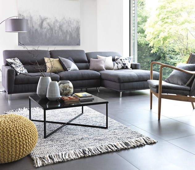 Large Grey Corner Sofa In Living Room Area With Scatter Cushions And Yellow Knitted Footstool