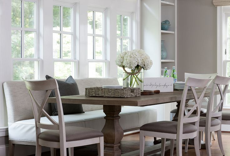 Chic, sophisticated dining room boasts a Restoration Hardware salvaged Wood Trestle Rectangular Extension Dining Table  lined with a light gray dining bench and white x-back dining chairs accented with taupe seat cushions placed in front of windows flanking tall built-in shelving.