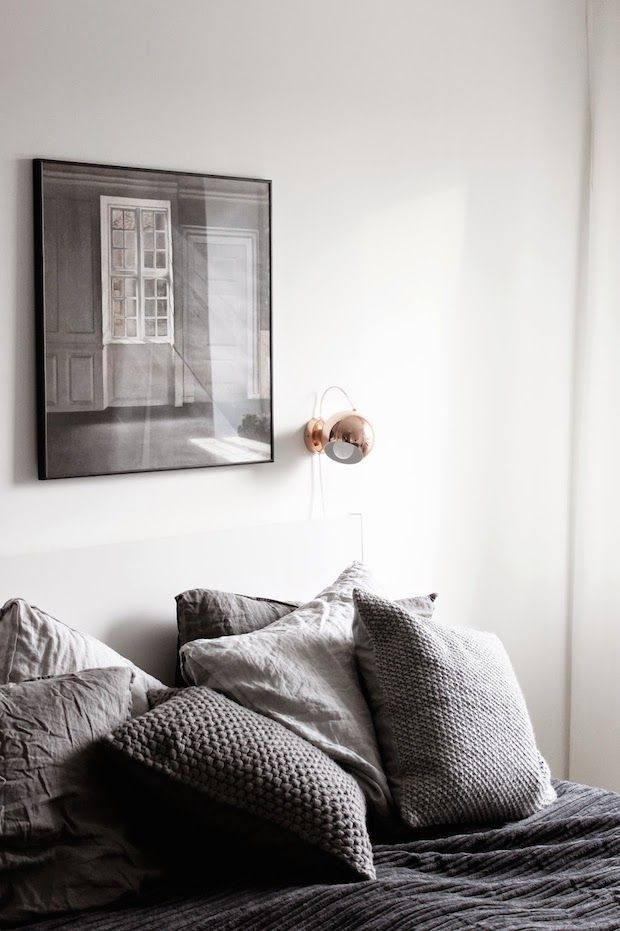 Copper reading light and dark grey bedding in the bedroom of a beautifully captured Danish home. Photography Johanne Dueholm