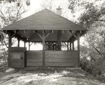 Vue générale de l'abri de pique-nique de l'île Adelaide, qui montre le toit en croupe, les chevrons apparents, les poteaux de soutien en bois et les consoles en bois, 1992.; Parks Canada Agency / Agence Parcs Canada / Historica Resources Ltd., 1992.