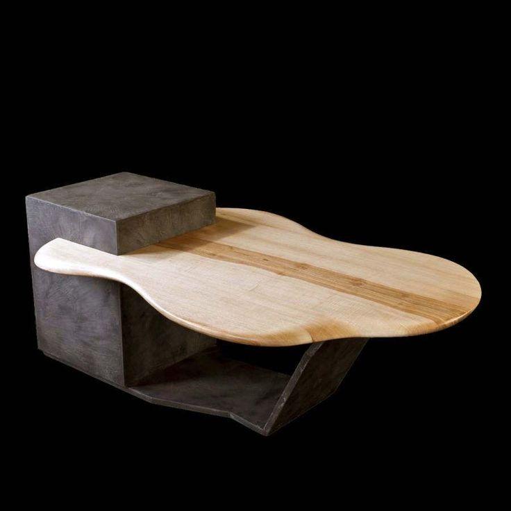 Dimensions : H 530/430 x 1300 x 800/400 mm  Le volume cubique et la tablette dynamique sont en décor béton ciré. Les lignes sont droites et rigides pour un matériau d'apparence froid et inerte.  Le béton représente ici la construction.  Le dessus en frêne massif est inspiré des galets de rivière avec lesquels on réalise des ricochets.  Les couleurs naturelles du bois ont offert un veinage irrégulier avec au centre une représentation de la rivière. L'érosion est traduite par un arrondi…