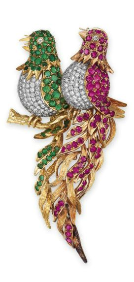 A RUBY, EMERALD AND DIAMOND BROOCH  Designed as two birds perched on a branch, each pavé-set with brilliant-cut diamonds, the head and wings pavé-set with circular-cut emeralds or rubies extending to the tail, mounted in 18k white, rose and yellow gold, 8.3 cm long