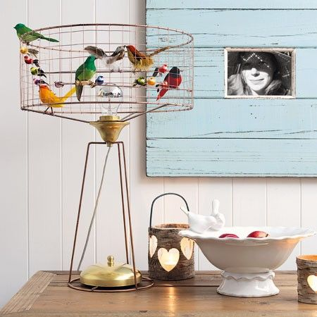 An addition to our bird cage lighting collection this striking and unique table lamp is home to a menagerie of pretty coloured birds made from real feathers. A truly beautiful and eye-catching lamp. As each lamp is individually hand made the colours and assortment of birds will be different to the photograph.