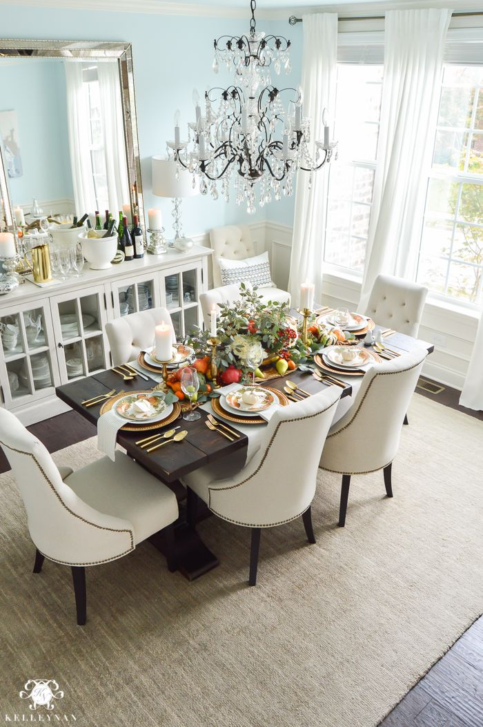 Thanksgiving Dinner Table Ideas - Gold Pottery Barn table setting with fruits, veggies, flowers, and eucalyptus - Elegant blue dining room with crystal chandelier and World Market linen lyida chairs with a Restoration Hardware trestle table and IKEA Ritva white curtain panels