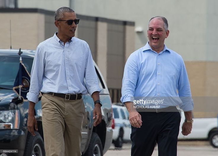 US President Barack Obama walks with Louisiana Governor John Bel Edwards (R)at…