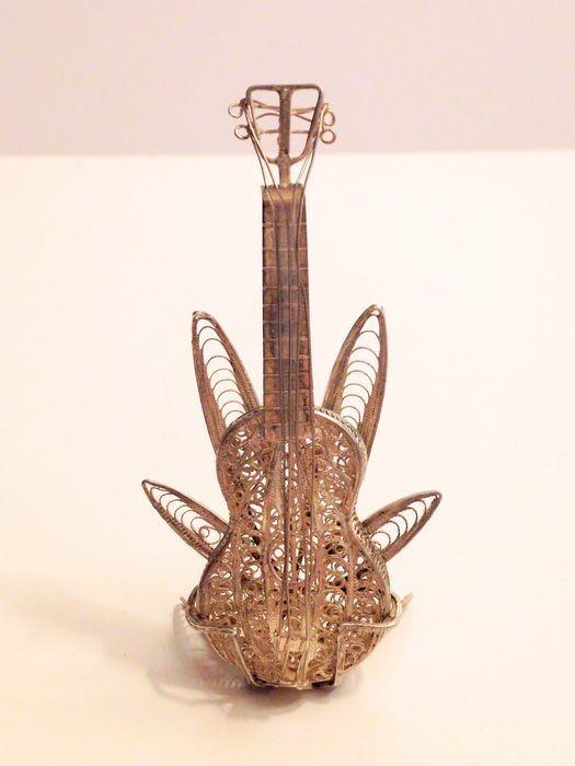 Zilveren filigraan gitaar met standaard 20e eeuw  Grote zilveren miniatuur gitaar met standaard Gemerkt met 1e gehalte zilver 950/1000 Geheel in uitstekend staat. Afmetingen: Gitaar L 7 cm X B 3 cm - standaard L 5 cm X B 4 cm Wegen totaal: 10 gram Word aangetekend & verzekerd verzonden.  EUR 1.00  Meer informatie