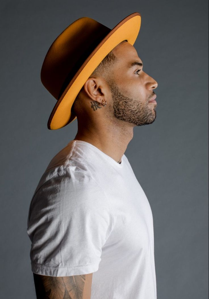 Zion wears hat Magill Fedora and t-shirt Frame Denim.