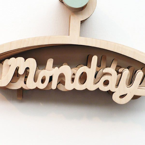 """Wooden coat hanger with the lower cross bar shaped like the word """"monday"""""""