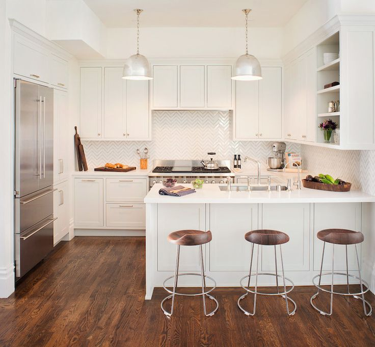Amazing kitchen with off-white cabinets paired with white quartz countertops and white chevron tile backsplash framing range hood concealed behind faux cabinet doors over high-end stainless steel range.