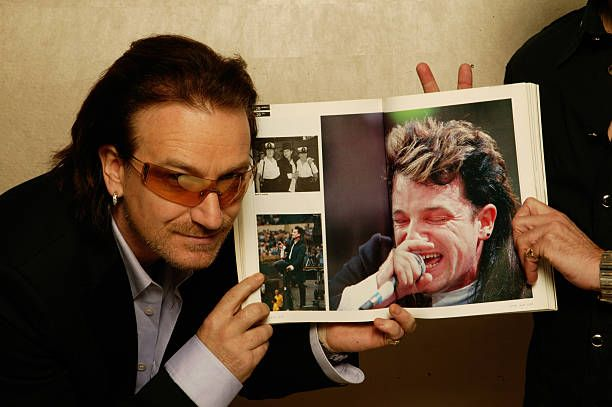 Bono 20 Years On -   At the Courthouse Hotel, London, England December 3, 2004, Irish singer Bono of U2, points to a picture of himself in a souvenir photo book of the 1985 Live Aid charity concert. Twenty years after its release, the original charity single, 'Do They Know It's Christmas', has been re-recorded and released under the name Band Aid 20 and featuring a contribution from Bono. U2 drummer Larry Mullen Jr is just visible at right. (Photo by Dave Hogan/Hulton Archive/Getty Images)