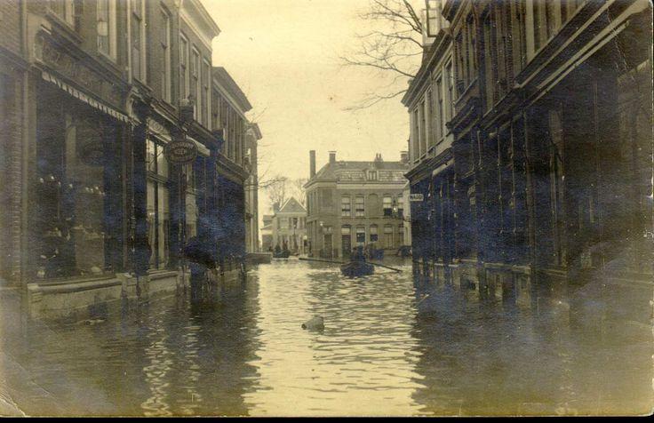 Hoog water (1916) in de Roggenstraat (links nrs 31-35) gezien naar de Vispoorten(draai) brug. In het midden en op de achtergrond roeibootjes. Links de winkel van de gezusters van Eijk, daarnaast J. Bergkamp, Boekbinderij.