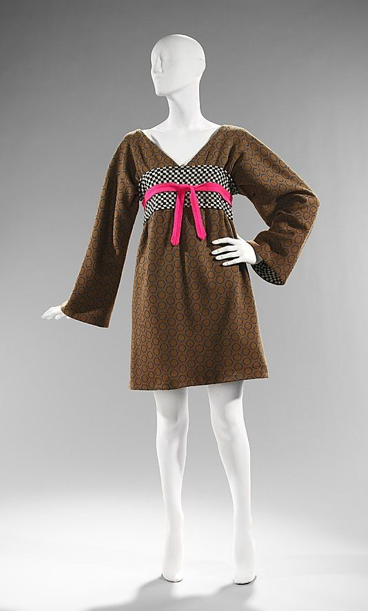 """Wool """"Kabuki Dress"""" by Rudi Gernreich, American, ca. 1963. Modeled by Gernreich's favorite model and muse, Peggy Moffitt, the """"Kabuki"""" dress combines aspects of traditional Japanese garments with geometric patterning. The kimono-style belt, traditionally at the natural waist has been raised, flattening the bust. The kimono sleeves are long and loose fitting and the skirt is considered short for the period. These design elements are characteristic, as he promoted youth and movement in dress."""