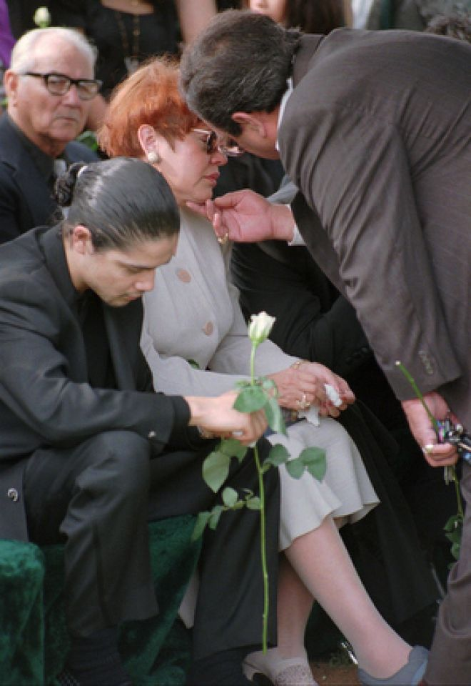 Father of slain Tejano music star, Abraham Quintanilla, right, consoles his wife, Marcella, as Chris Perez, husband of Selena, bows his head during funeral services Monday, April 3, 1995, in Corpus Christi.