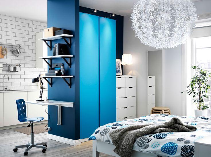 Een slaapkamer met een kast in het wit met blauwe deuren in combinatie met een witte kist met zeven lades.
