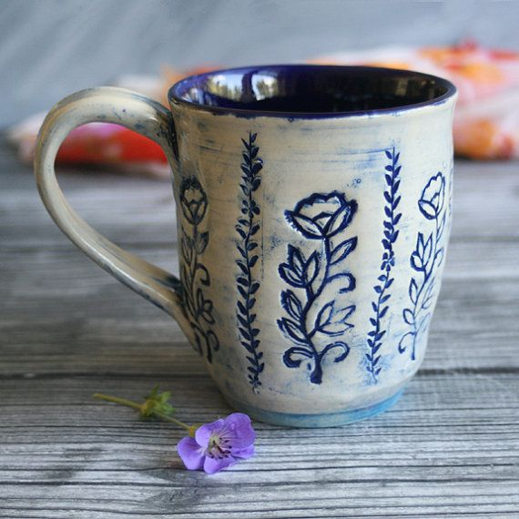 This extra large mug was hand thrown and trimmed on my potters wheel using a white stoneware clay. It was then stamped with various wooden stamps and bisque fired. It was glazed with a dark blue underglaze on the exterior and then with a clean wet sponge wiped clean to leave the underglaze only in the impressed design (the white color is the natural color of the stoneware). A shiny navy blue glaze was used on the inside and a clear transparent was painted on the exterior, it was then fired…