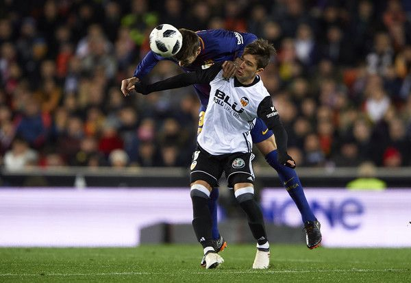 Luciano Vietto of Valencia competes for the ball with Gerard Pique (L) of Barcelona during the Copa de Rey semi-final second leg match between Valencia and Barcelona on February 8, 2018 in Valencia, Spain.