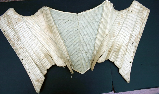 Lacing on stays was very fashionable in the 1760s, this example has not only lacing but also a fashion fabric forepart. Sign of the Golden Scissors