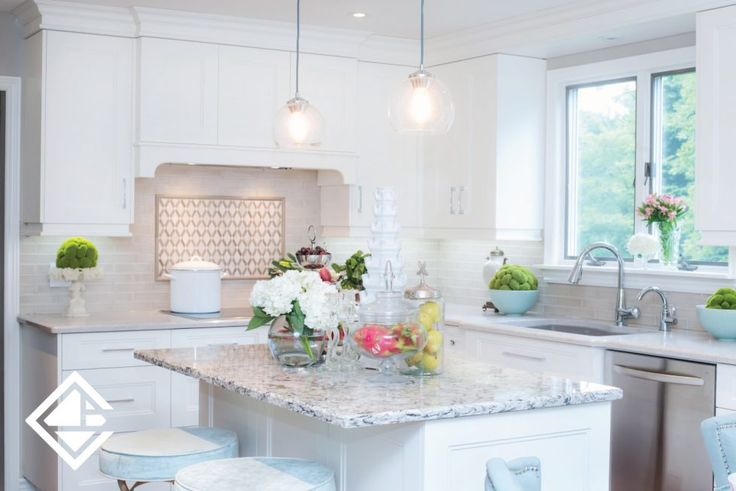 This classic kitchen is a dream come true. We just love this gorgeous granite counter top with the classic white custom made cabinets. Love the detailed back splash above the stove.
