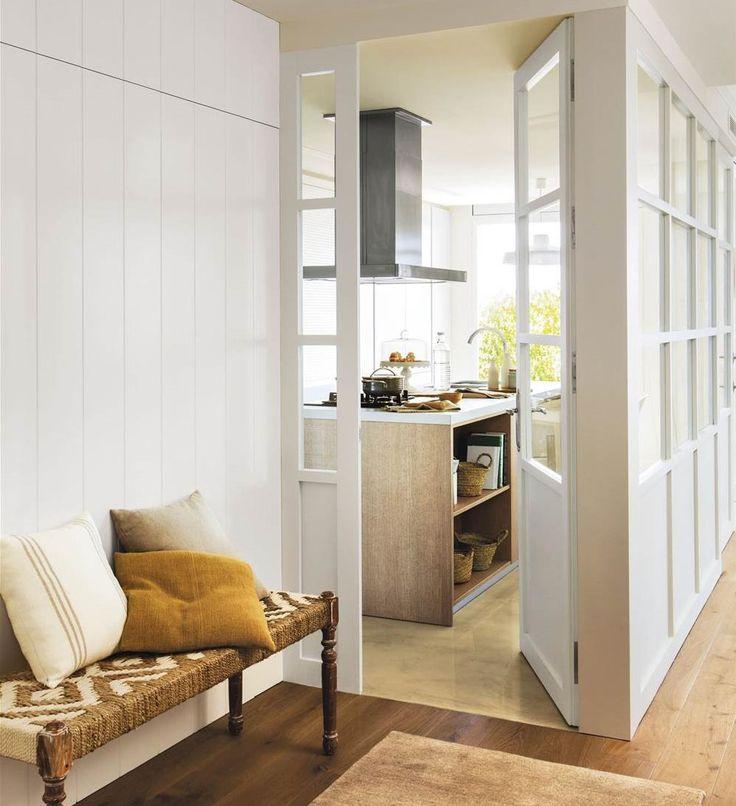 recibidor con pared forrada en madera blanca y puertas de cristal que llevan a la cocina