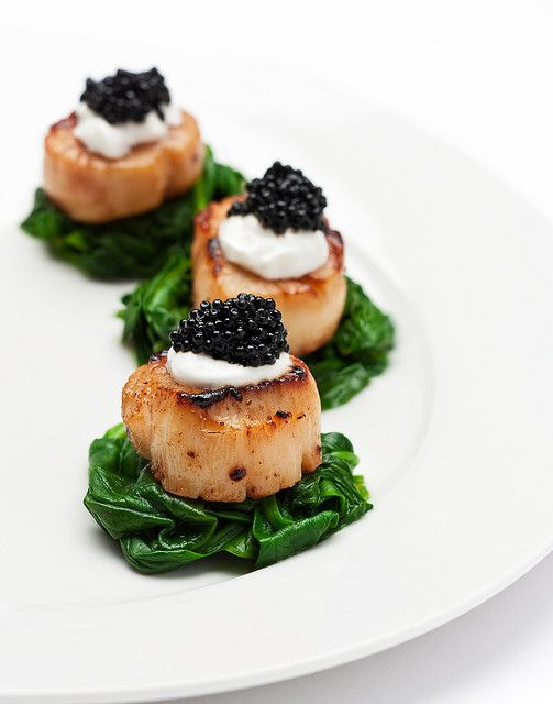 Caviar Scallops: pan-seared sea scallops on a bed of baby spinach, topped with sour cream and caviar