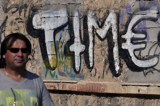 A man walks past graffiti featuring the word 'Time' but using the Euro sign in place of the letter 'e'on a wall in Athens on June 15, 2015. (LOUISA GOULIAMAKI/AFP/Getty Images) | Athens' Badass Street Art