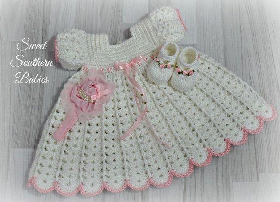 Elk meisje moet een witte jurk in haar kledingkast. Gemaakt met een zachte lichtgewicht baby garen en gegarneerd met een verstelbare roze satijnen lint bij de taille en de mouwen. Deze set bevat de jurk, Mary Jane schoenen en een roze roos hoofdband verfraaid met parels.  Mary Jane schoenen zijn alleen gemaakt om te passen tot 5 voeten ***  3 maanden: borst 18, Shoulder to zoom 15-inch 6 maanden: borst 18.5, Shoulder to zoom 15.5 9 maanden: borst 19-inch, schouder tot Hem: 16 12 maanden…