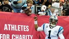 Cam Newton gives a young boy a football and fist bump