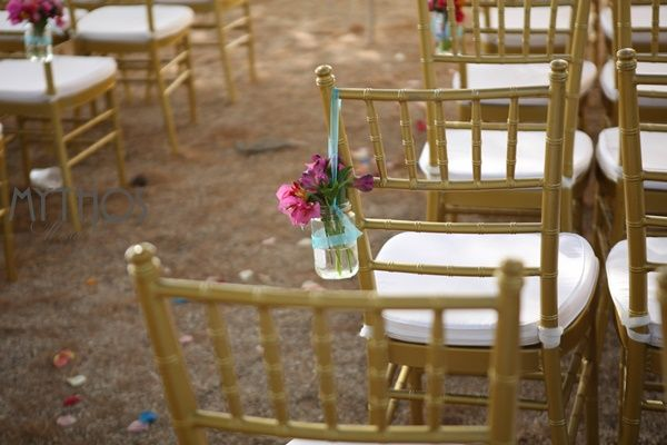 Wedding ceremony set up - gold tiffany chairs decorated with small vases with colorful flowers on the aisle chairs #weddingflowers #weddingdecoration #chairdecoration #weddingingreece #kefaloniawedding