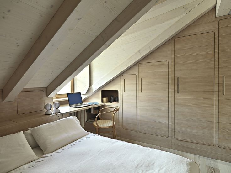 Cozy master bedroom in the attic with built in closet and sloped walls/ceiling…