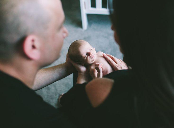 photo of newborn baby in between parents