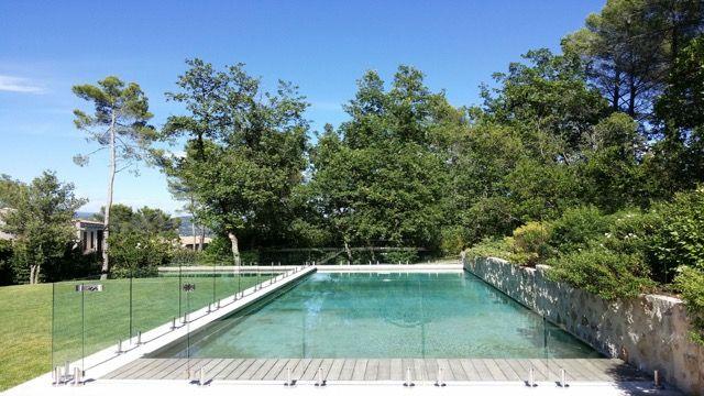 Barrière de piscine en verre Securit 12mm maintenu par de discrets pieds en inox L316, la clôture la plus discrète du marché