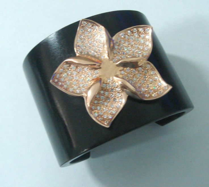 Artisan hand made wooden cuff with gold plated silver madagascar periwinkle flower. This beautiful periwinkle flower is studded with high quality cubic zirconia or swarovski crystals. This cuff will definitely stand out!