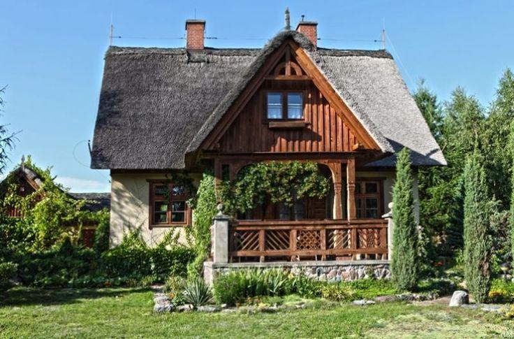 drewniany dom ze słomianą strzechą