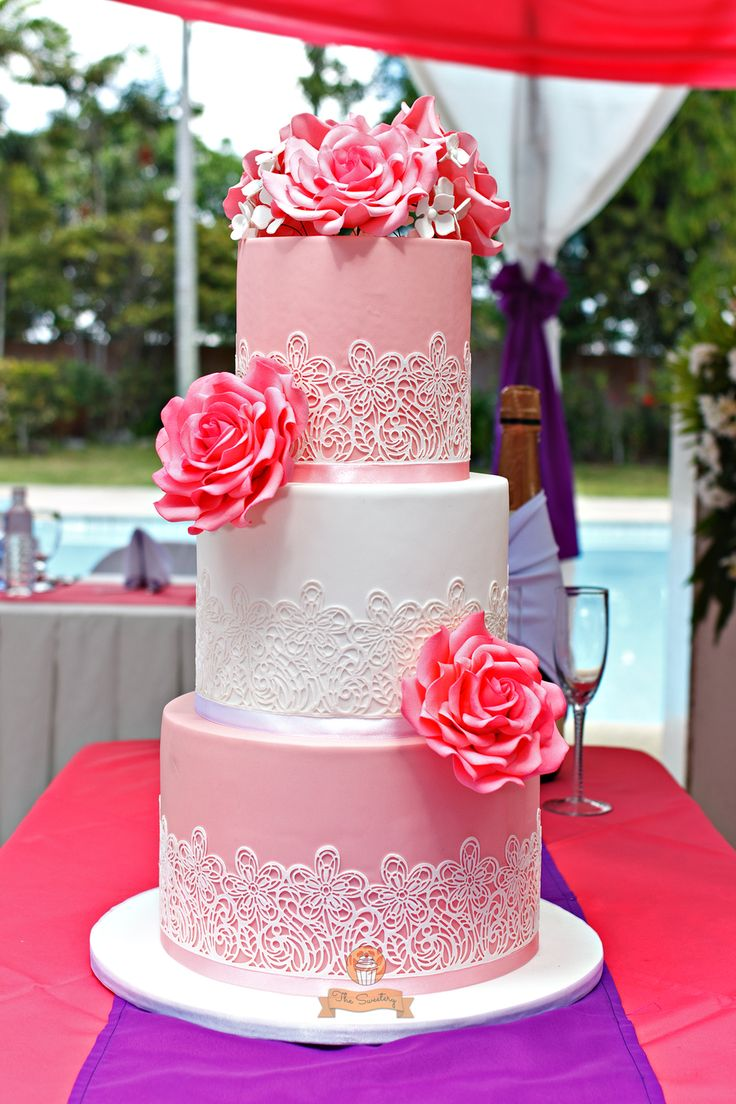 3-tier pink wedding cake adorned with sugar laces and pink...