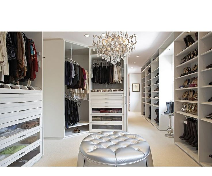 a walk in closet featuring white cabinetry with many storage options a glowing chandelier