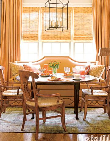 Peachy shades of orange set the mood in this cheerful North Carolina breakfast room by designer Kathy Smith. The banquette is in a washable faux-leather. The curtains are in Henley by Rogers & Goffigon. The chandelier is vintage.