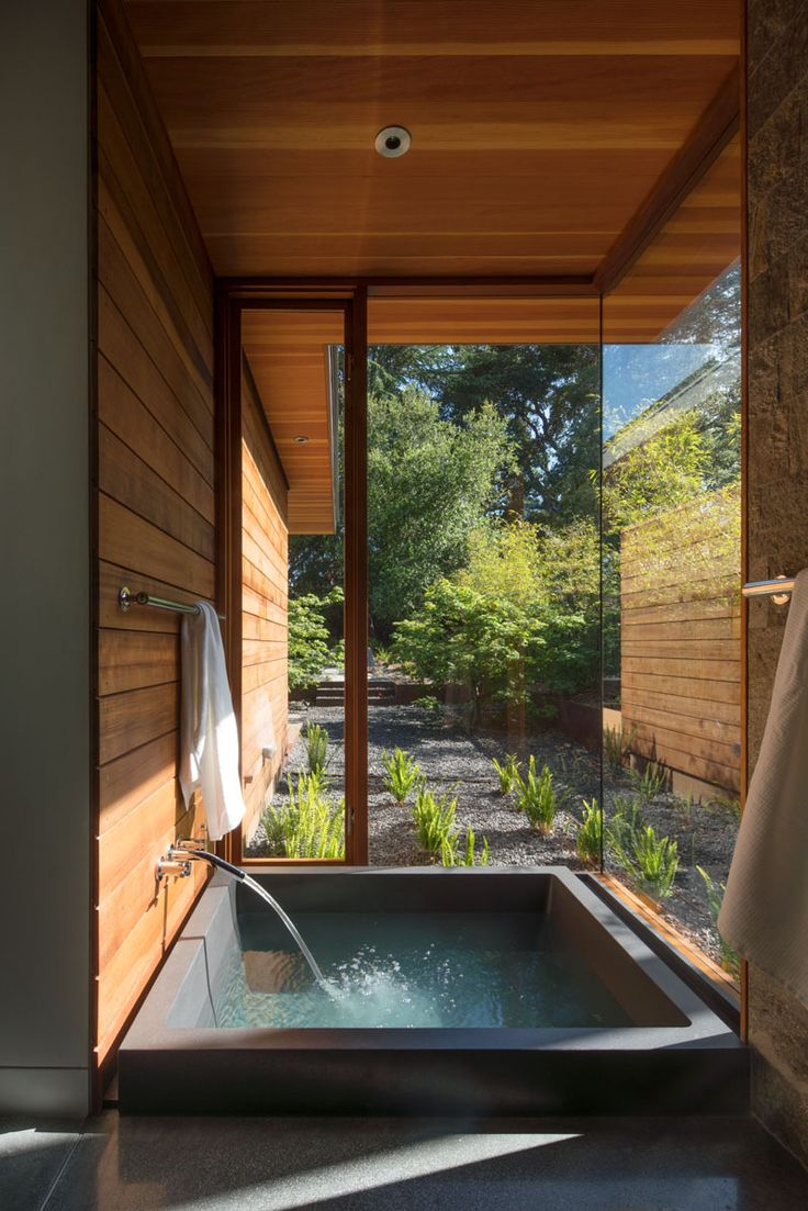 In the ensuite bathroom off the master bedroom in this modern house, is a private spa that's sunken down into the floor and looks out to the garden through the floor-to-ceiling windows.