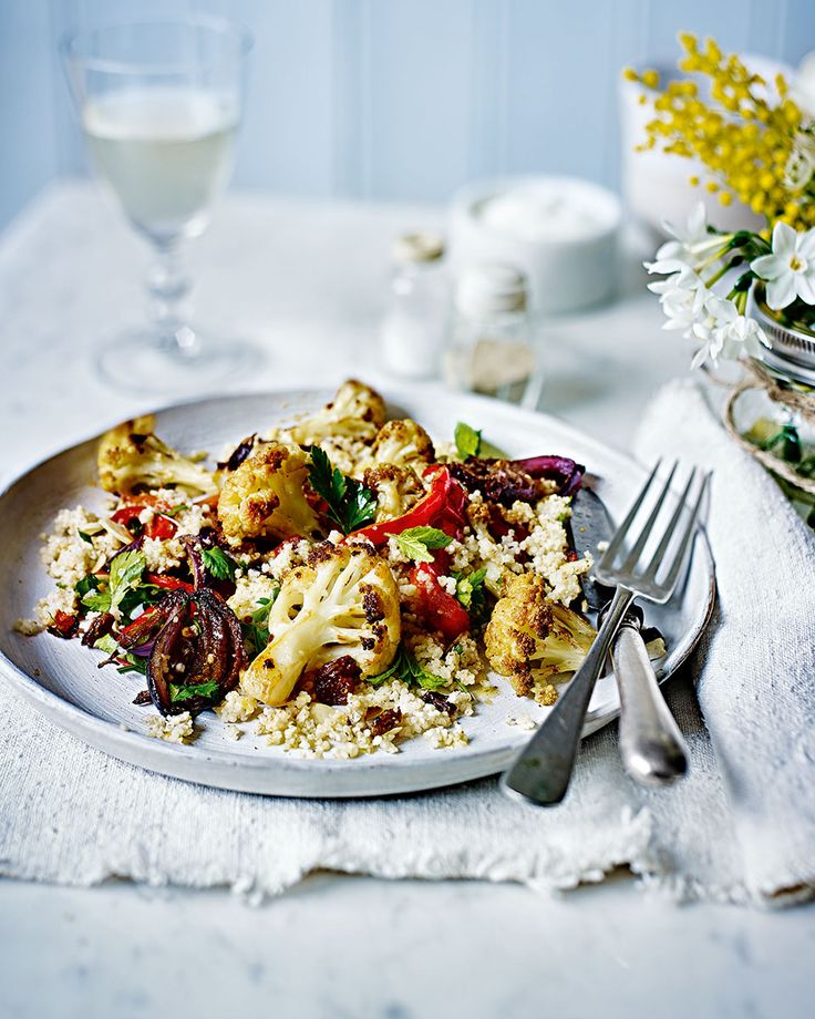 Roasted cauliflower, onion and pepper are served on a bed of fluffy couscous and drizzled with a tahini and herb dressing in this Middle-Eastern inspired vegetarian recipe.