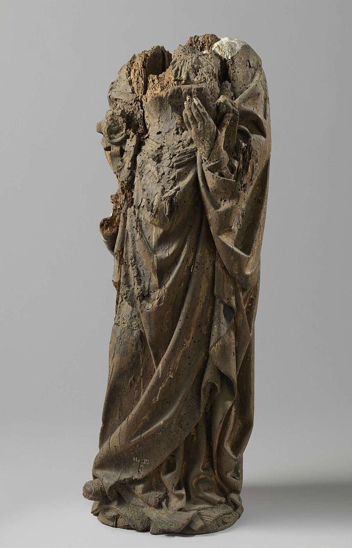 Anonymous | Vrouwelijke heilige, Anonymous, c. 1515 - c. 1520 | Zij staat met de rechtervoet iets naar voren op een grondje en houdt in de linkerhand een fragment van een opengeslagen boek. Onder het keurs met uitgeschulpte halsuitsnijding en met mouwen, voorzien van splitten, een dun geplooid hemd. Van de schouders hangt de mantel, die bij de armen is opgenomen. Onder de rok van het keurs de stompe rechterschoenpunt en deel van onderkleed. Voor het middel een afhangende sjerp. Het hoofd…